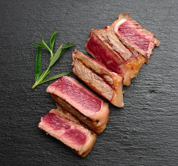 Smażony stek wołowy new york w plastrach na czarnej powierzchni, rzadki stopień wypieczenia, widok z góry
