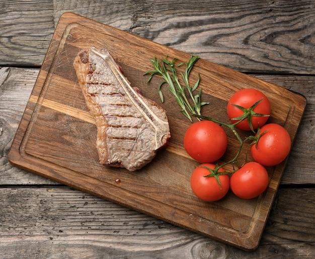 Smażony stek wołowy nowojorski rostbef na drewnianej desce do krojenia, rzadki stopień wysmażenia, widok z góry