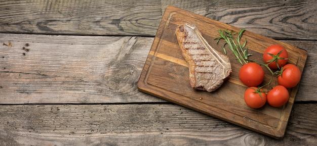 Smażony stek wołowy nowojorski rostbef na drewnianej desce do krojenia, stopień wysmażenia krwisty, miejsce na kopię
