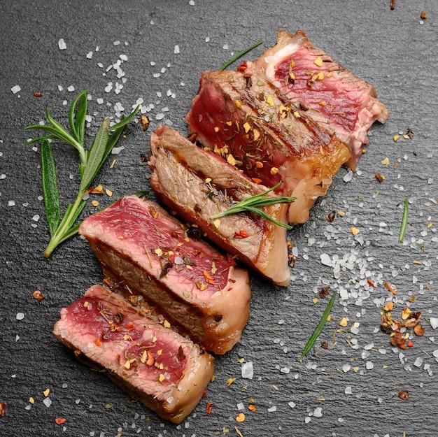 Smażony stek wołowy w plastrach rostbef nowojorski z przyprawami, rzadki stopień wypieczenia, widok z góry