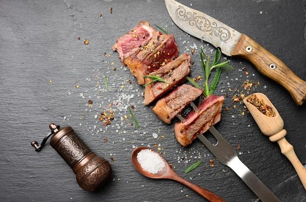 Smażony stek wołowy w plastrach z przyprawami, rzadki stopień wypieczenia, widok z góry
