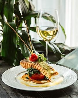 Smażony stek z łososia umieszczony na krążkach ziemniaka pomidor i brokuły