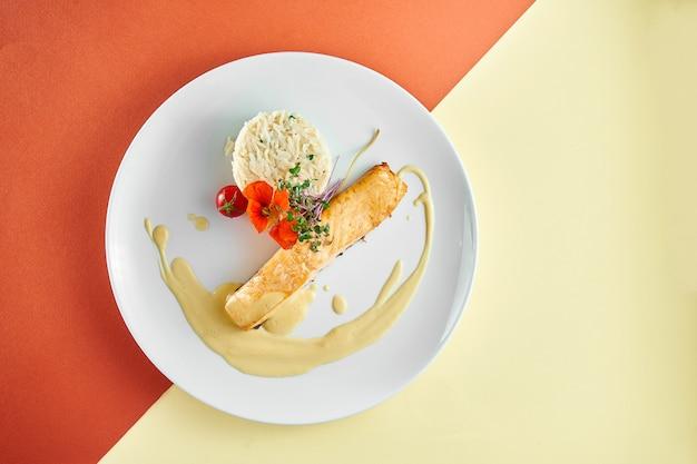 Smażony stek z łososia z żółtym sosem i ryżem na przystawce w białym talerzu na kolorowej powierzchni.