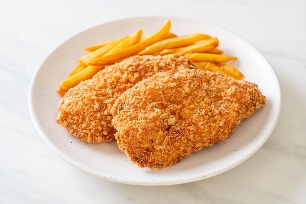 Smażony stek z piersi kurczaka z frytkami i keczupem