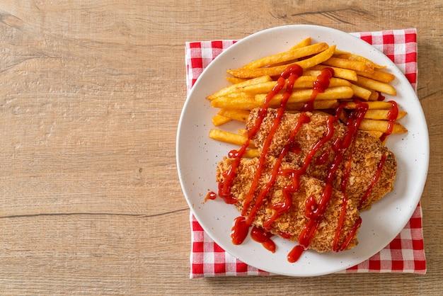 Smażony stek z piersi kurczaka z frytkami i ketchupem