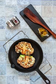 Smażony stek ze świeżego kalafiora na patelni. pośredni etap przygotowania.