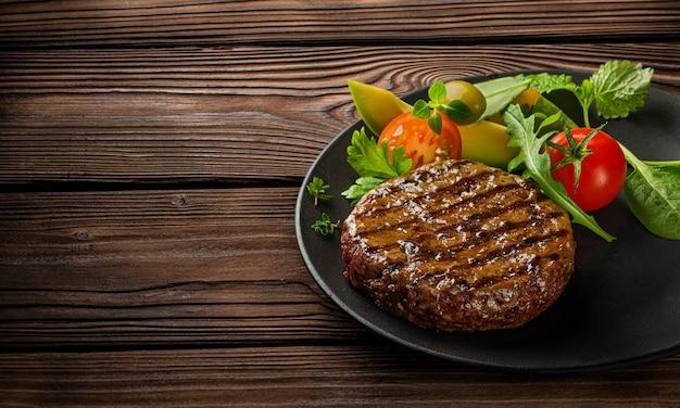 Smażony świeży duży burger wołowy z sałatką i ziołami na czarnym talerzu na drewnianym stole