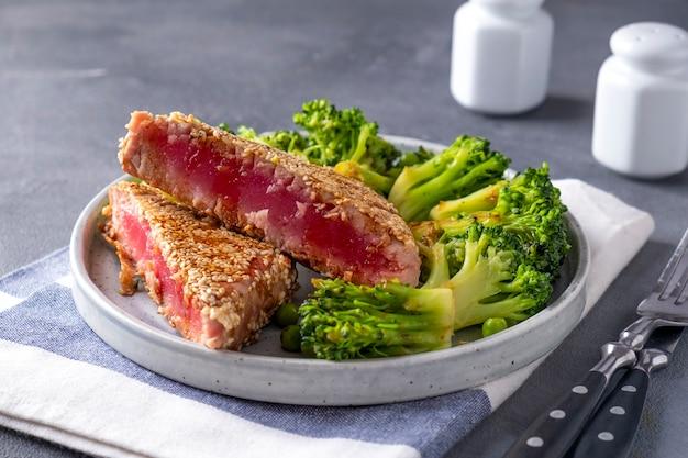 Smażony tuńczyk z brokułami i zielonym groszkiem. tuńczyk smażony z warzywami. zdrowe jedzenie