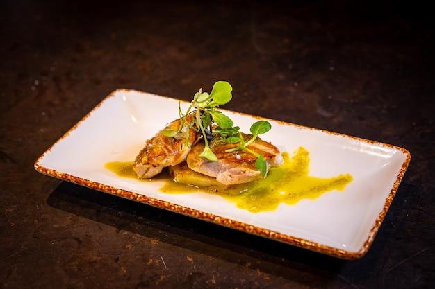 Smażony tuńczyk z sosem na czarnym tle, na białym talerzu