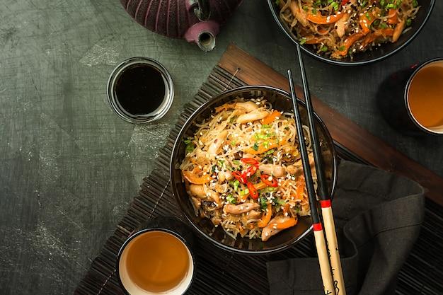 Smażony w woku makaron wymieszać z kurczakiem i warzywami na talerzu