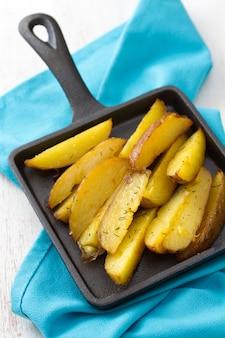 Smażony ziemniak na czarnej patelni i niebieskiej serwetce