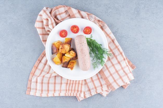Smażony ziemniak z kiełbasą na białym talerzu.