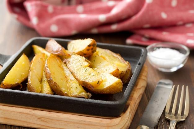 Smażony ziemniak z solą, widelcem i nożem