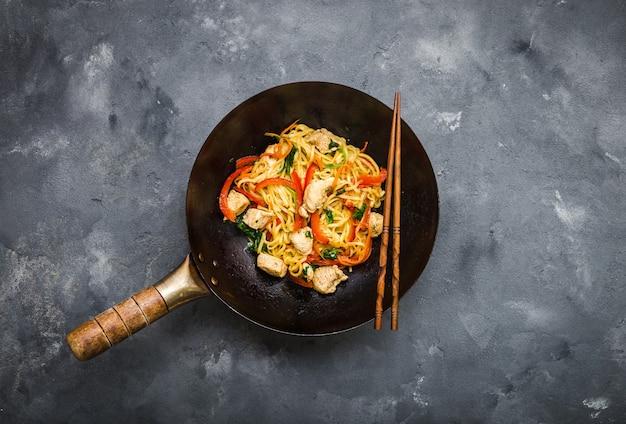 Smażyć makaron, tradycyjny chiński wok, pałeczki. makaron azjatycki z warzywami, kurczakiem.
