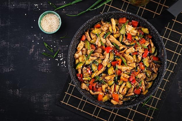 Smażyć na mieszadle z kurczakiem, cukinią i słodką papryką - chińskie jedzenie. widok z góry, powyżej