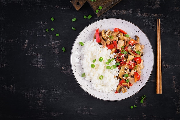 Smażyć z kurczakiem, pieczarkami, słodką papryką i gotowanym ryżem. chińskie jedzenie. widok z góry, powyżej