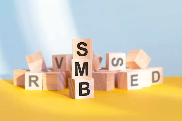 Smb napisane na drewnianych kostkach - ułożone w pionową piramidę, szare i żółte tło, smb - skrót od server message block, koncepcja biznesowa