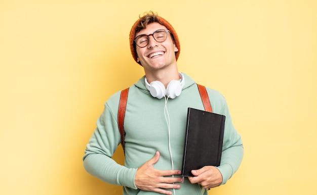 Śmiać się głośno z jakiegoś przezabawnego żartu, czuć się szczęśliwym i wesołym, dobrze się bawić. koncepcja studenta