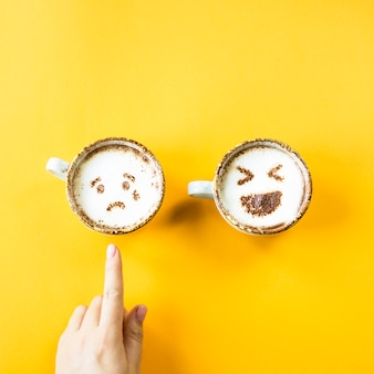 Śmiech i smutek emoji są rysowane na kubkach cappuccino na żółtym tle