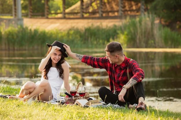 Śmiech. kaukaska młoda, szczęśliwa para spędzając razem weekend w parku w letni dzień