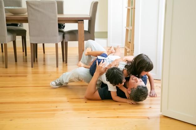 Śmiech ojca leżącego na podłodze i przytulanie uroczych dzieci.