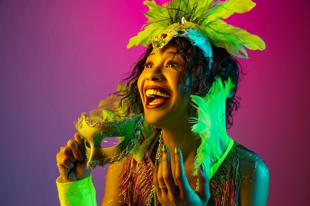 Śmiech. piękna młoda kobieta w karnawałowym, stylowym stroju maskarady z piórami tańczącymi na gradientowym tle w neonowym kolorze. koncepcja obchodów świąt, świąteczny czas, taniec, impreza, zabawa.