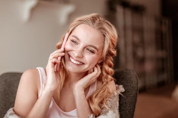 Śmiech podczas rozmowy. zalotna długowłosa kobieta rozmawiająca przez telefon komórkowy i bawiąca się z bliskim przyjacielem