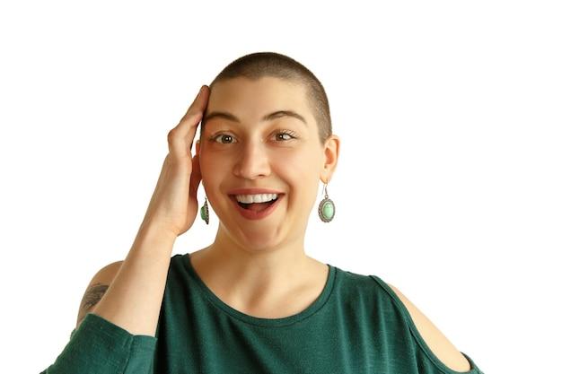 Śmiech. portret młodej kobiety rasy kaukaskiej z zakręconym wyglądem na białej ścianie. niezwykły wygląd z tatuażami i łysiną. ludzkie emocje, wyraz twarzy, sprzedaż, koncepcja reklamy. kultura młodzieżowa.
