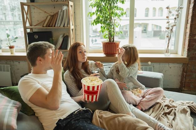 Śmiech. rodzina spędza miło czas razem w domu, wygląda wesoło i wesoło. mama, tata i córka bawią się, jedzą popcorn, oglądają telewizję. razem, domowy komfort, miłość, koncepcja relacji.