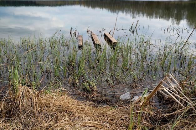 Śmieci na brzegu jeziora. plastikowe torby i butelki zanieczyszczają środowisko. paleta drewniana w wodzie. pojęcie ochrony i zachowania otaczającej przyrody.