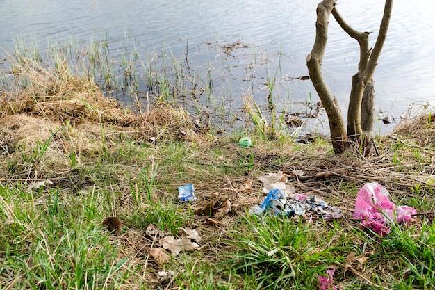 Śmieci na brzegu jeziora. plastikowe torby i butelki zanieczyszczają środowisko. pojęcie ochrony i zachowania otaczającej przyrody. zdjęcie wysokiej jakości