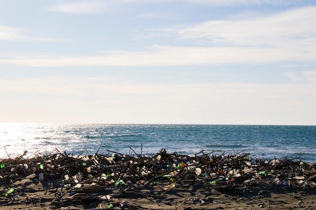 Śmieci na piaszczystej plaży, zanieczyszczenie plastikiem i metalami, globalne ocieplenie i zanieczyszczenie wody