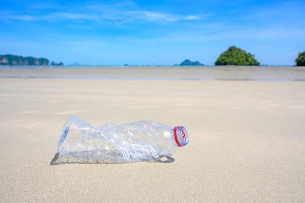 Śmieci na plaży plastikowa butelka morska leży na plaży i zanieczyszcza morze i życie morskiego życia rozlane śmieci na plaży dużego miasta.