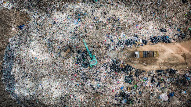Śmieci na wysypisku śmieci lub wysypisku śmieci, widok z lotu ptaka śmieciarki rozładowują śmieci na wysypisko śmieci, globalne ocieplenie.