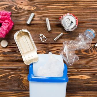 Śmieci nadające się do recyklingu umieszczone nad pojemnikiem na śmieci