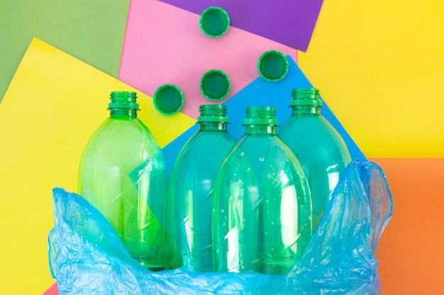 Śmieci, plastikowe butelki w plastikowej torbie, na kolorowym tle abstrakcyjnym. ekologia i zanieczyszczenie planety ziemia. sortowanie śmieci.