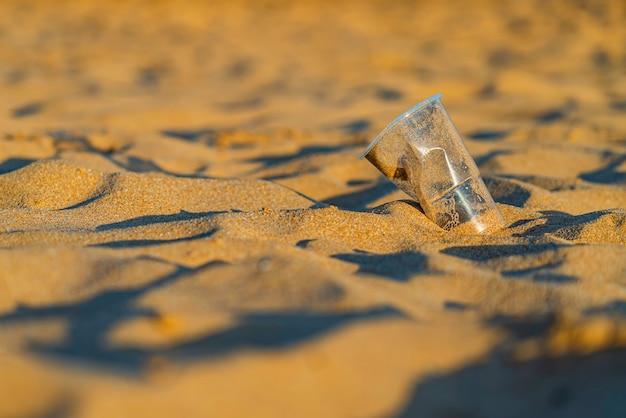 Śmieci plastikowy kubek na złotym piasku plaży oceanu, playa de las teresitas, teneryfa. koncepcja ochrony środowiska. zanieczyszczenia mórz i oceanów odpadami z tworzyw sztucznych. recykling.