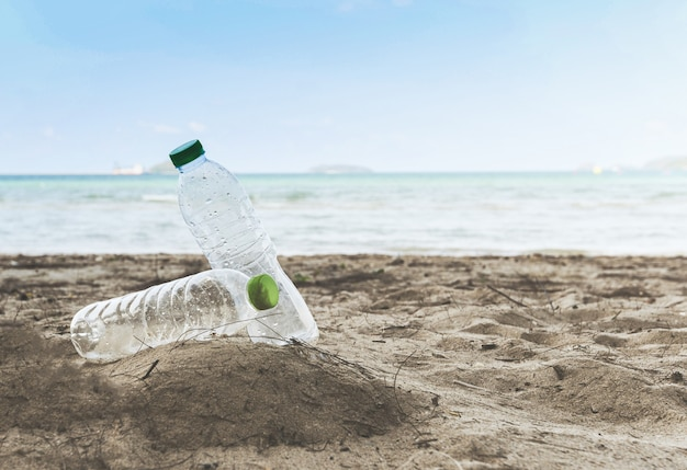 Śmieci w morzu z plastikową butelką na plażowym piaskowatym brudnym morzu na wyspie