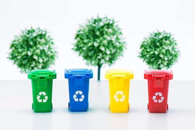 Śmieci w pojemnikach na śmieci na tle zielonych drzew. pojęcie zanieczyszczenia. uratuj planetę.