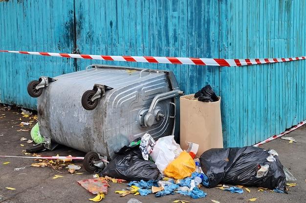 Śmieci w przeładowanych odwróconych koszach na śmieci na ulicy miasta.