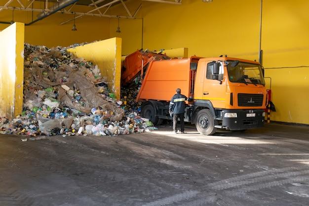 Śmieciarka rozładowuje śmieci w fabryce recyklingu odpadów.