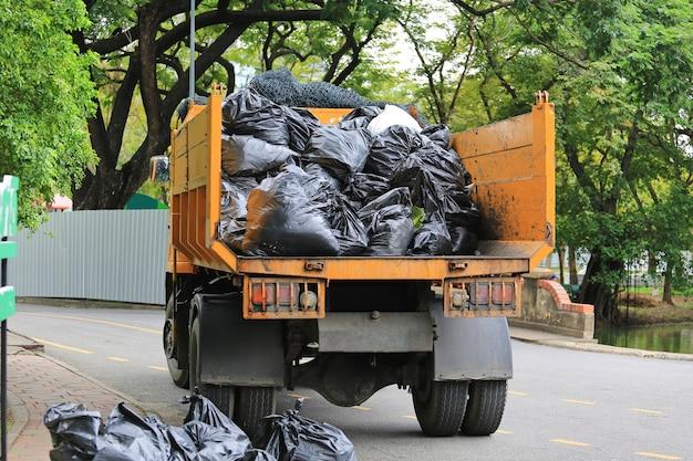 Śmieciarka z ładowaniem odpadów w parku ogrodowym.