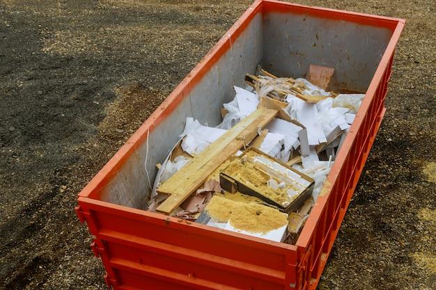 Śmieciarki budowlane w metalowym pojemniku, remont domu.
