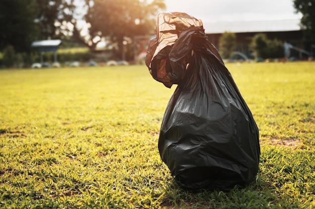 Śmieciarska czarna torba na trawie z światłem słonecznym