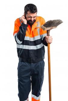 Śmieciarz zakrywający uszy