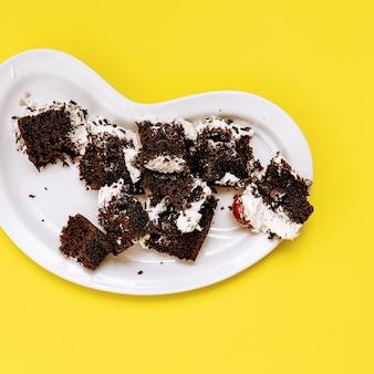 Śmieciowe ciasto czekoladowe na żółtym tle. płaska sztuka cukierków waniliowych?