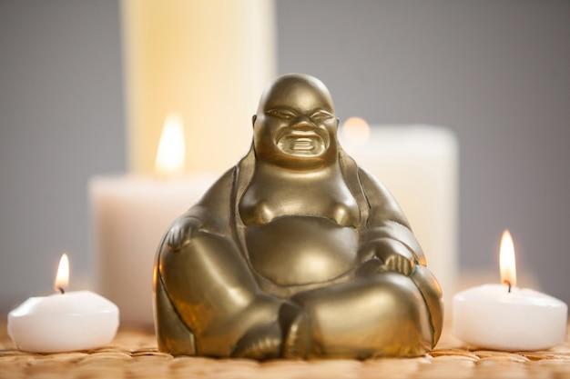 Śmiejąc figurka buddy i zapalone świece na matę