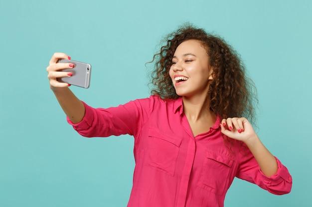 Śmiejąc się afryki dziewczyna w różowe ubrania dorywczo robi selfie strzał na telefon komórkowy na białym tle na tle niebieskiej ściany turkus w studio. ludzie szczere emocje, koncepcja stylu życia. makieta miejsca na kopię.