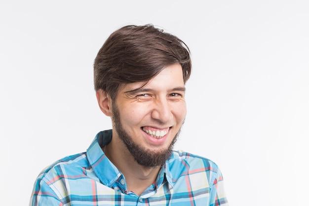 Śmiejąc się brodaty przystojny mężczyzna na białym tle z miejsca na kopię