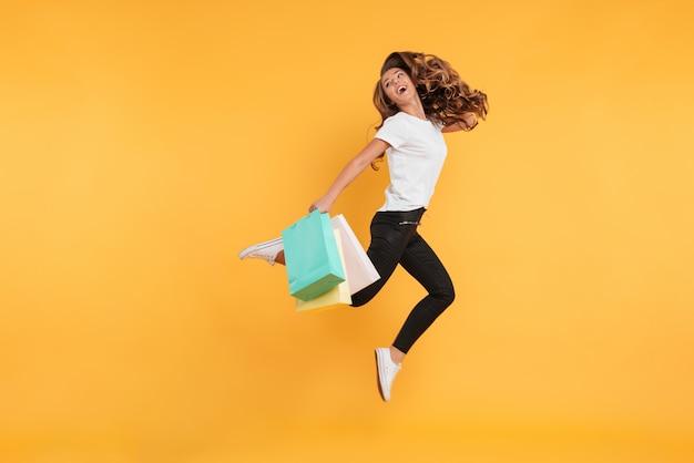 Śmiejąc się całkiem młoda kobieta skoki gospodarstwa torby na zakupy.